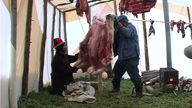 Two Innus arranging the skin of the caribou for the degreasing process