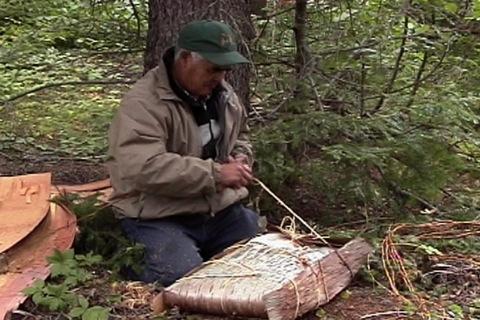 il attache la viande séchée d'un caribou entier dans un contenant d'écorce avec des racines