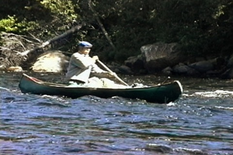 he descends the rapids in a canoe