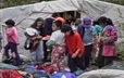 Jeunes de l'école Arc-en-ciel de Montréal en avant d'une tente à Mani-utenam