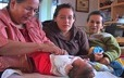Grandmother, mother and aunt gathered around a newborn infant