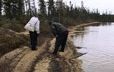Two hunters analyzing tracks in the sand near a lake