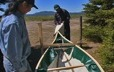 Two men adjust the outer shell of a traditional canoe