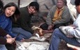 An Ekuanitshit elder teaches some youth how to make bread in the sand