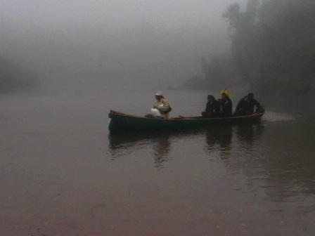 One Innu and three Kayapo in a canoe on the Mingan River