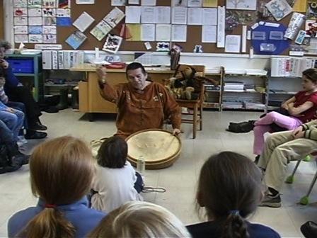 Paul-Émile Dominique explique le tambour traditionnel à des jeunes