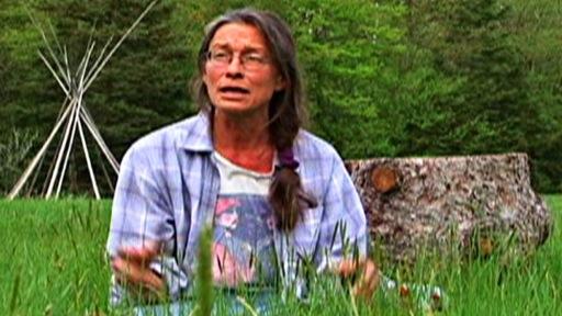 Femme assise par terre dans un champ près de Kahnawake au Québec