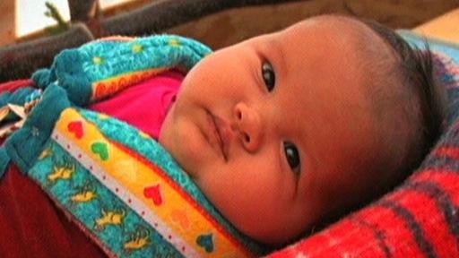 Gros plan d'un bébé emmailloté dans une couverture traditionnelle