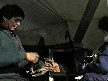 Zacharie Bellefleur teaches Messenak Bellefleur to start a fire in the tent stove