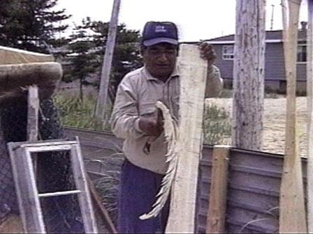 À l'aide d'une hache, un homme fend une planche de bois pour en faire une rame