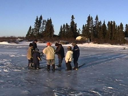 Sur la glace d'un lac en début d'hiver, on s'apprête à percer un trou pour pêcher