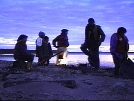A group of Innu rests by a fire in the early morning