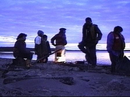Près d'un feu au petit matin, un groupe d'Innus se repose
