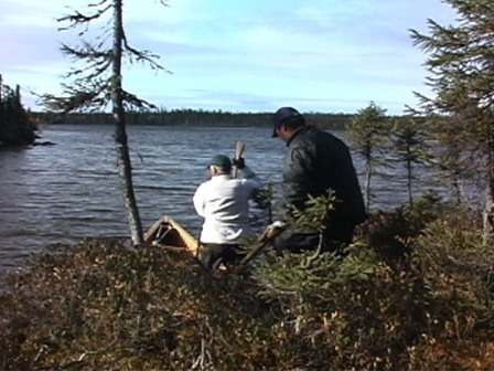 Two hunters prepare to launch their canoe