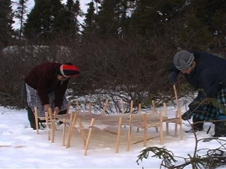À l'extérieur, à quelques pouces de la neige, deux femmes étendent une peau de caribou pour la faire geler