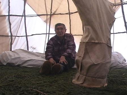 À l'intérieur d'une tente, une femme inspecte l'installation servant à boucaner une peau de caribou