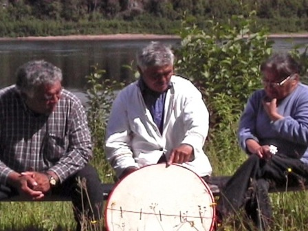 Jean-Baptiste Bellefleur explains to two friends how to make a traditional drum