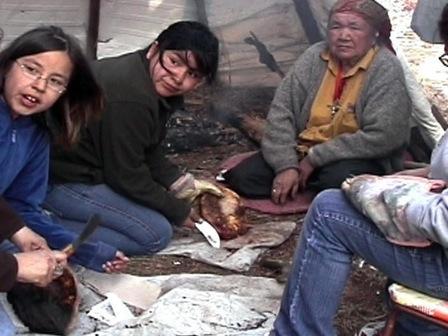 Une aînée d'Ekuanitshit enseigne à des jeunes à faire du pain dans le sable